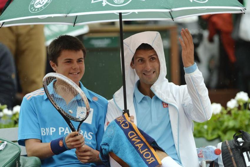 La pluie empêche peut-être Novak Djokovic de jouer au tennis, mais ne l'empêche pas de faire sourire le public en plaisantant et trinquant avec un ramasseur de balle pendant la pause.